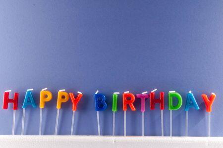 Muchas velas de colores con texto feliz cumpleaños Foto de archivo