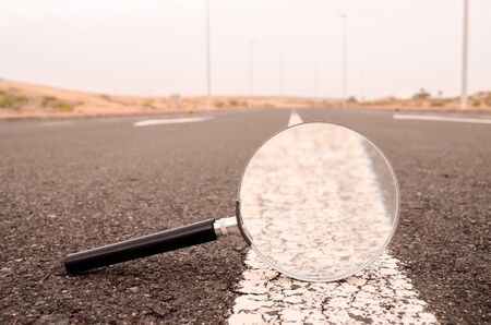 Travel Concept Magnify Glass Loupe on the Asphlat Road 스톡 콘텐츠