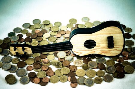 Picture of a Business Money Concept Idea Coins and Guitar Banco de Imagens