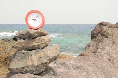 One Red Clock on the Rocks Near the Ocean 免版税图像
