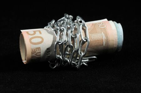 Money in chains that represents the crisis on a black background