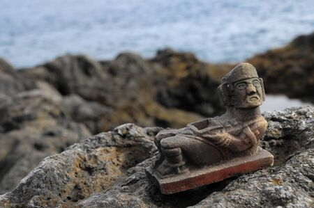 Ancient Maya Statue on the Rocks near Ocean