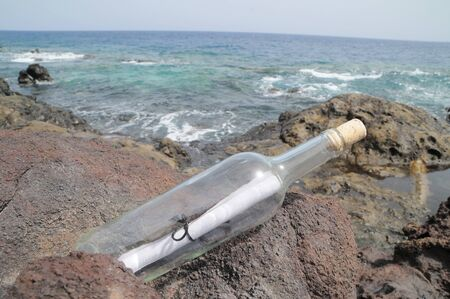 Message in the Bottle on the Rocks near the Beach