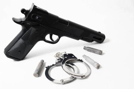 Pistol Gun and Handcuffs on a White Background