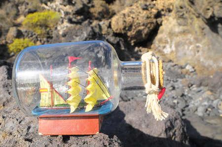 Ancient Spanish Sailing Boat in a Bottle near the Ocean Standard-Bild