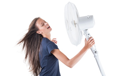 swelter: Young woman cooling herself under wind of cooler fan isolated on white background