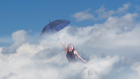 Flying girl with umbrella in the blue blue sky  photo