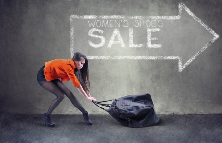 foot model: Beautiful woman carrying heavy bag  with some difficulty Stock Photo