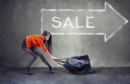 handbags: Beautiful woman carrying heavy bag  with some difficulty Stock Photo