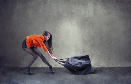Beautiful woman carrying heavy bag  with some difficulty photo