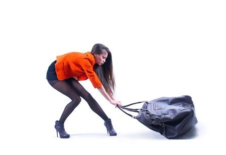 Mulher bonita bolsa de transporte pesado com alguma dificuldade