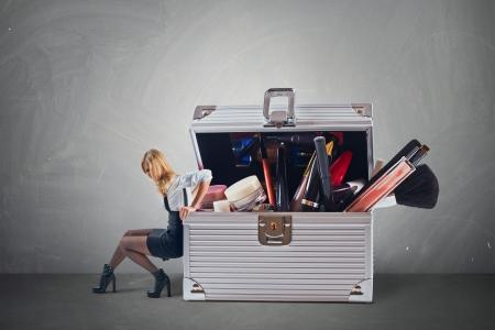 Jonge aantrekkelijke vrouw duwen grote hevy geval is met cosmetica met enige moeite Stockfoto