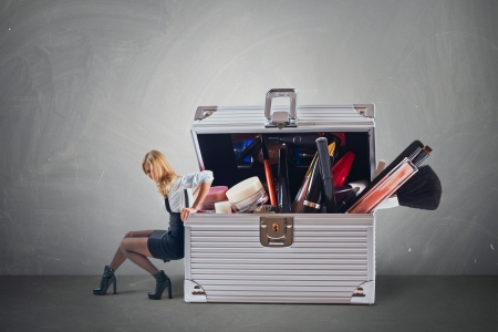 cosmetics bag: Young attractive woman pushing big hevy case with cosmetics with some difficulty  Stock Photo