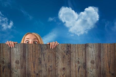 neighbour: curious hide woman   girl, cloud heart shape, blue sky background  Stock Photo