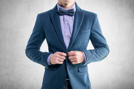 Красивый элегантный молодой человек в моде пальто классического костюма смокинг и галстук-бабочку. Фото со стока