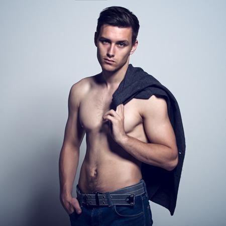 naked man: Cuerpo musculoso sin camisa elegante desnuda chico deportivo en topless hombre macho atlético sexual con un torso desnudo en jeans azul Foto de archivo
