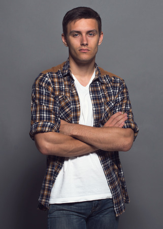 Portrait of a handsome young man - student urban casual stule, checkered shirt, arms crossed
