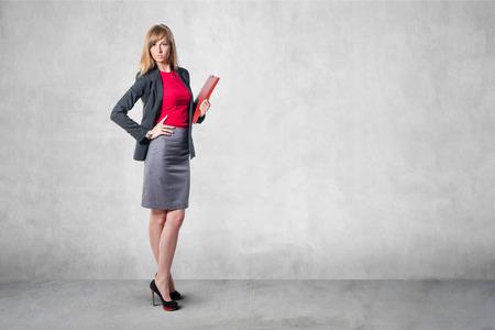 Portret van jonge zakenvrouw met een rode map grijze rok overhemd klassieke kostuum staande in de buurt van betonnen wand Stockfoto