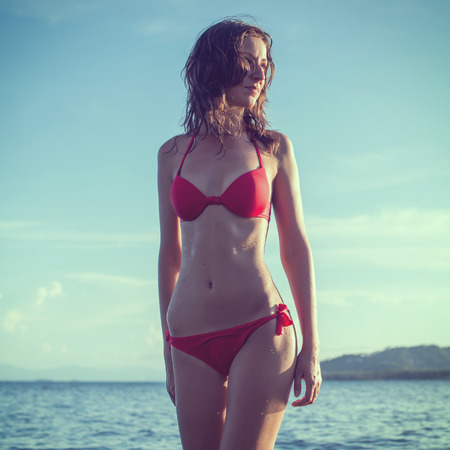 Red panties: Outdoor summer outdoor portrait of young pretty woman girl standing in red bikini swimsuit  Stock Photo