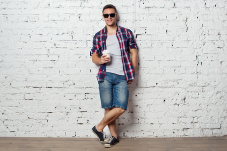 catchy: Bright young man hipster on vacation enjoying the day with coffee.