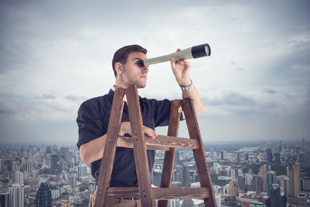 Young businessman looking for opportunities through the spyglass standing on the stairs Foto de archivo