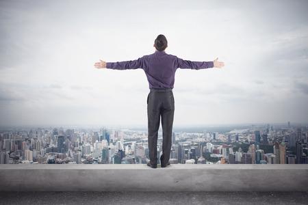 紫色のシャツと、市内の壮大なビューの前に両側に彼の手で屋根の端に trausers 立っている自信を持ってのビジネスマン。