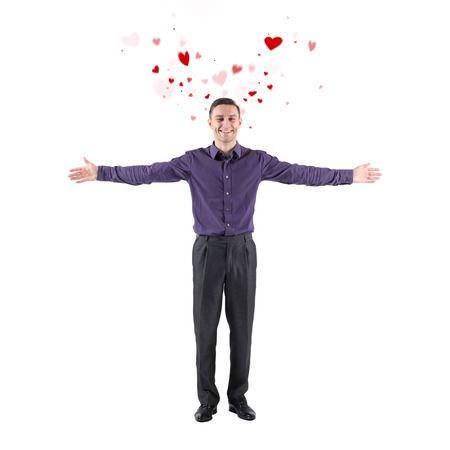 love declaration: Lovely young man declaration of love welcoming you on white background with flying hearts around with hands on the sides. Stock Photo