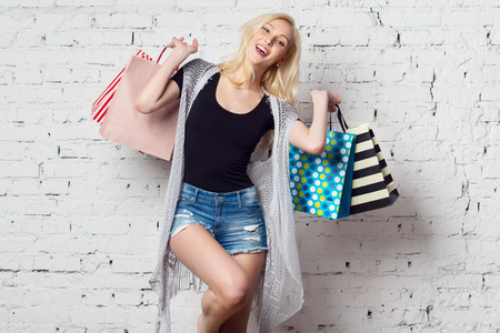 short shorts: Adorable blond girl against the wall with shopping bags with new purchases laughing out loud wearing summer clothes. Stock Photo