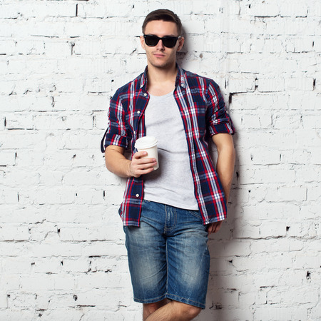 catchy: Handsome stylish young man in jeans shorts and shirt. Brutal man with a bristle, sunglasses and cofee. brick wall. Stock Photo