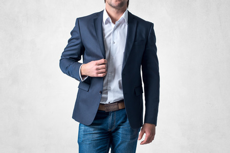 ropa casual: Hombre en traje de moda de pie por sí sola celebración de su chaqueta con confianza. Foto de archivo