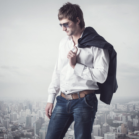 seducer: Confident, ambitious good looking man on the top of the city with a jacker on his shoulder Stock Photo