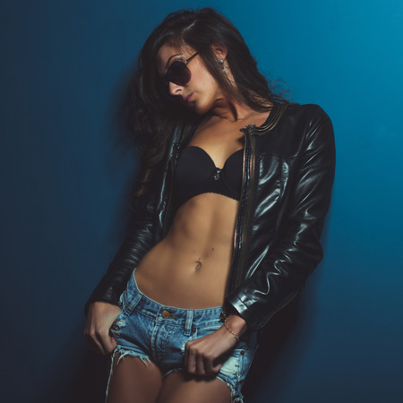 Awesome glamour cool girl young woman posing against the wall in stylish clothes denim jeans shorts, leather jacket.