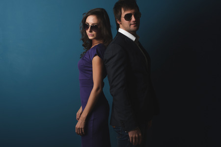 Perfect spy couple man and woman in glasses  standing back to back posing