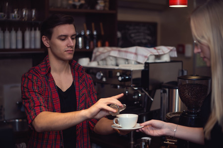 adds: Hipster barista in  plaid shirt adds cinnamon in customers cofee Stock Photo