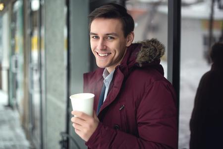 generoso: Hombre de negocios joven en una chaqueta y el invierno está bebiendo el café caliente a fría calle con vapor y brillante sonrisa en su rostro