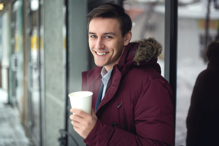 generous: Young businessman in a suit and winter coat is drinking hot coffee at cold street with steam and bright smile on his face