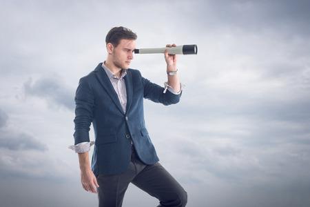 若い魅力的なハンサムな実業家付近の雲の側に立って、小型望遠鏡を通して見る新しい視点を見つけること 写真素材