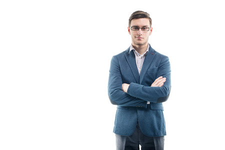 cross arms: Young strong businessman  in fashionable suit stands against the wall with hands crossed