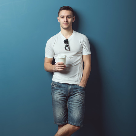 handsome young man: Young attractive handsome man in white t-shirt and jeans denim shorts standing against the wall and smiling holding coffee.