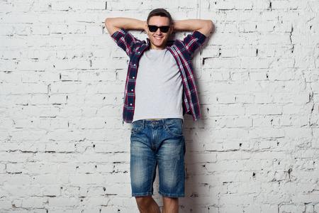 bel homme: Jeune homme avec des lunettes de soleil sourit heureux avec ses mains derri�re sa t�te.