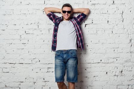 easygoing: Young man in with sunglasses smiles happily with his hands behind his head.
