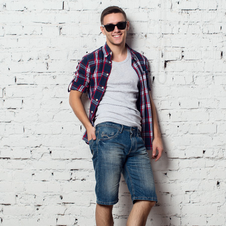 catchy: Handsome stylish young man in jeans shorts and shirt. Attractive hipster  with a bristle,sunglasses.