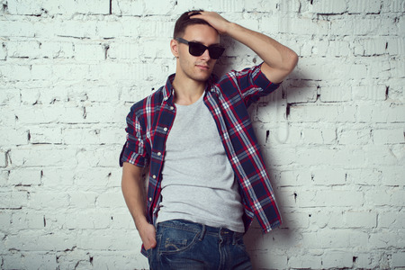 Casual gut aussehend attraktiver Mann hipster Kerl mit Sonnenbrille mit der Hand im Haar Standard-Bild