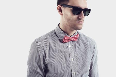 beau jeune homme: Jeune homme avec hipster rouge arc-cravate et des lunettes de soleil confiant et certained, regard sérieux