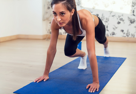 Young determined confident slim woman doing exercises on the blue mat looking straight forward