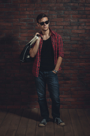 unbuttoned: Young hipster man wearing sunglasses casual clothes unbuttoned shirt and denim jeans with bag over shoulder standing near brick wall with hand in the pocket and looking away.