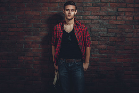 unbuttoned: Hipster serious man casual clothes unbuttoned shirt and denim jeans standing near brick wall hand in the pocket looking at camera.