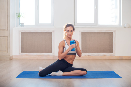 Beautiful athletic sporty woman sitting on yoga mat after some exercises with blue shaker in her hand  and white towel photo