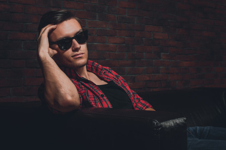 tempter: Portrait handsome young hipster man glasses casual clothes unbuttoned shirt sitting relaxing leaning on leather luxury sofa looking at the camera.