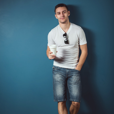 standing against: Young attractive handsome man in white t-shirt and jeans denim shorts standing against the wall and smiling holding coffee.